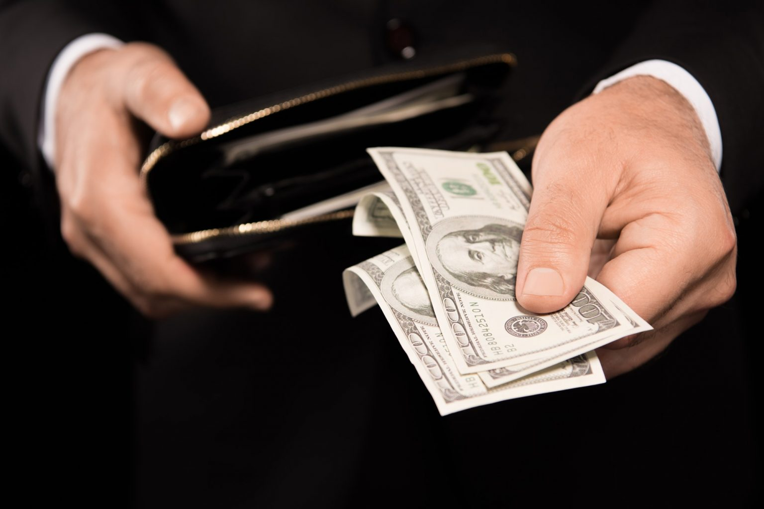 Cropped shot of male hands taking out money from the wallet